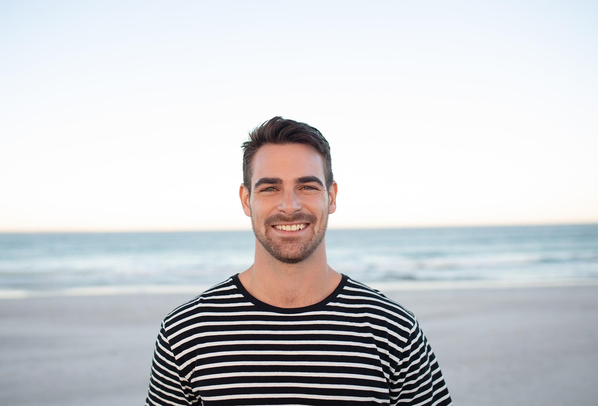 Hombre joven sonriendo con fondo de playa