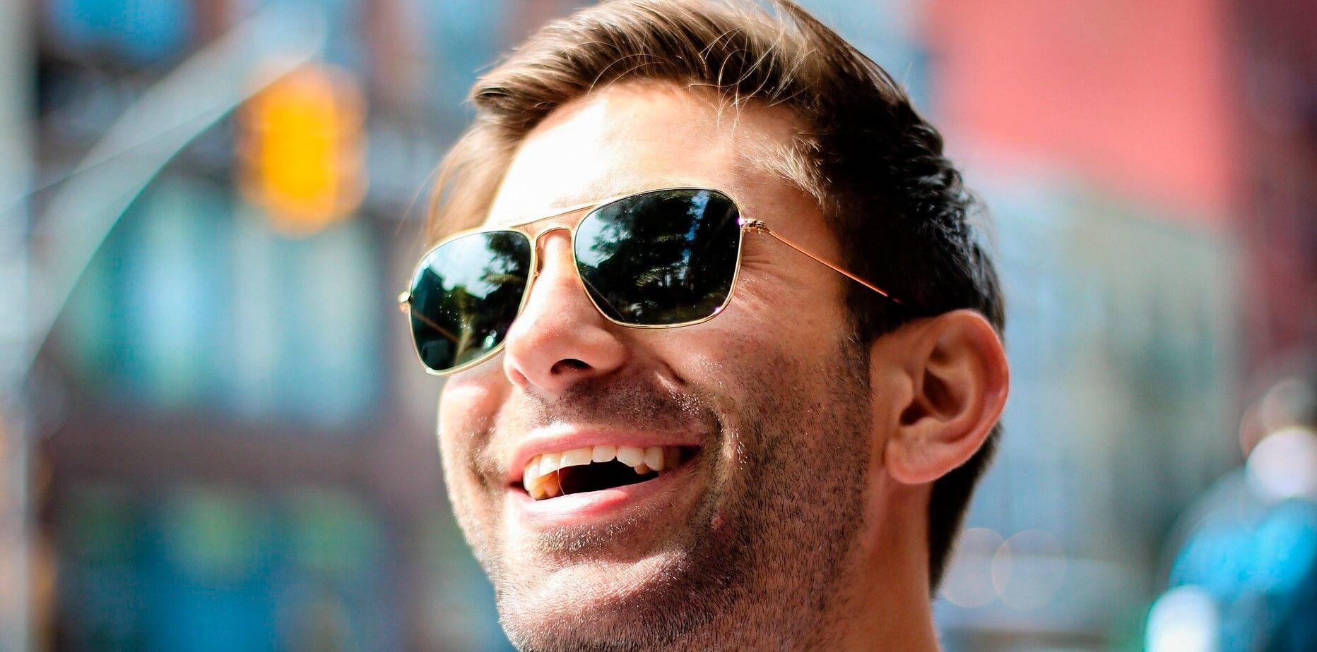 hombre feliz con gafas de sol sonríe en la ciudad
