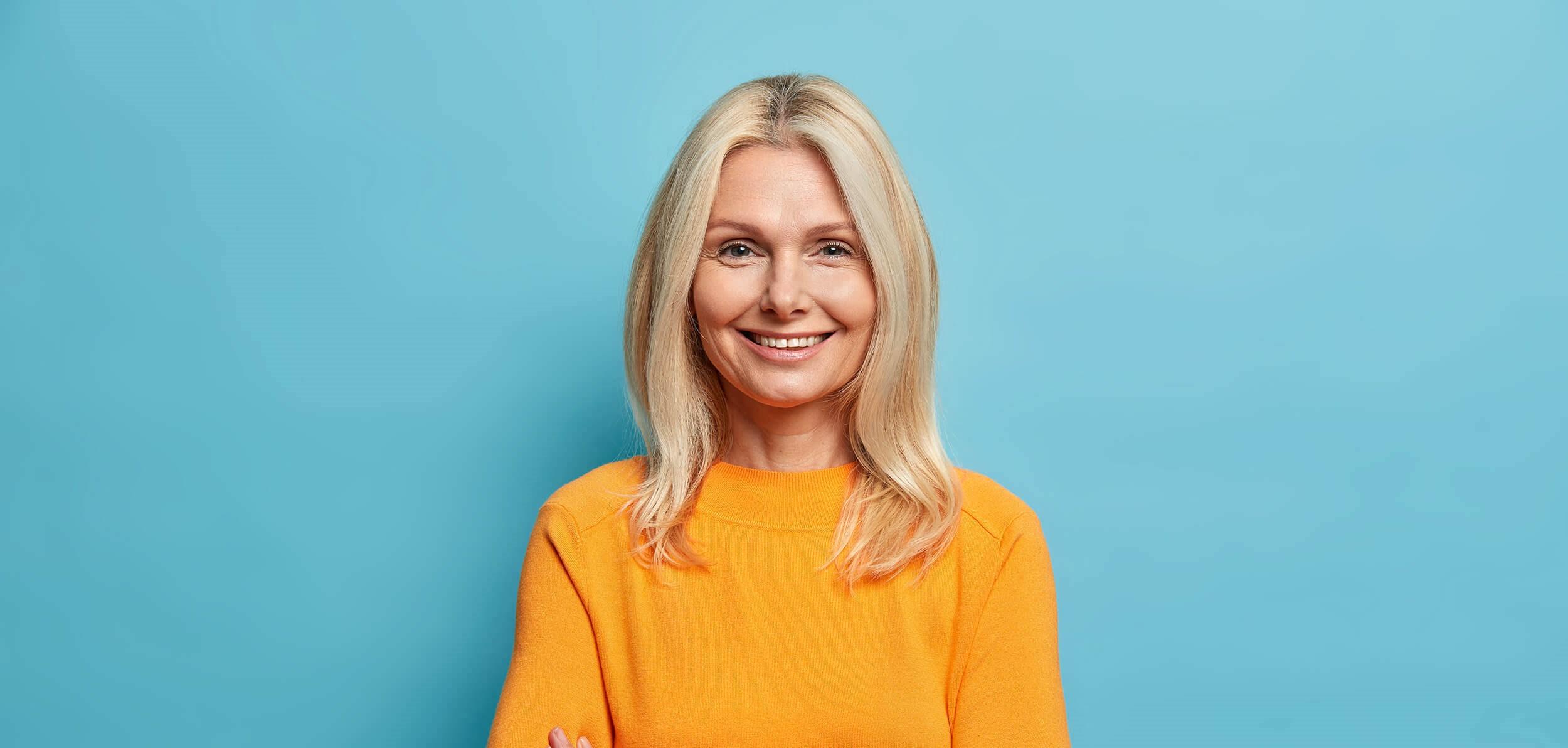 mujer madura con bonita sonrisa y dientes blancos con fondo azul