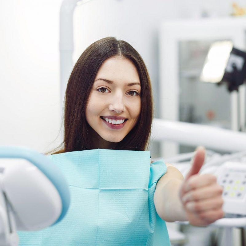 Mujer joven sonriendo positiva en dentista